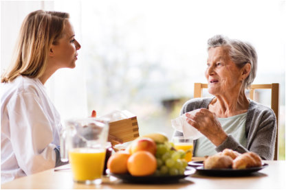 caregiver and an elderly woman talking in the dining table