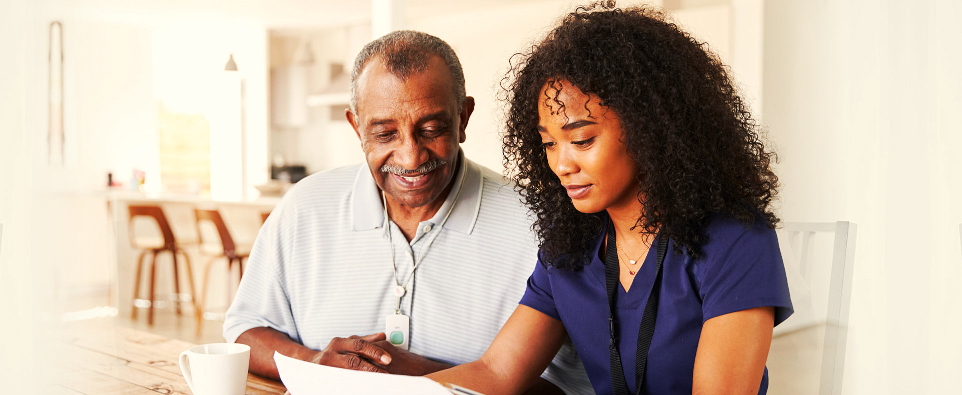 caregiver helping an elderly man with his papers