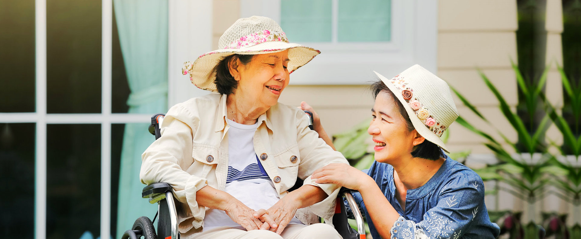 caregiver and an elderly woman on a wheelchair chatting