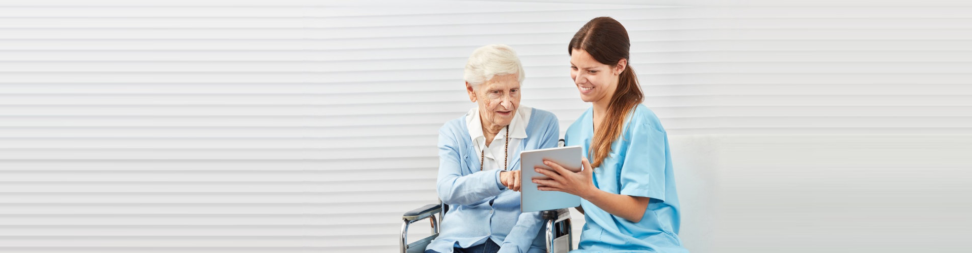 caregiver helping an elderly lady with her ipad