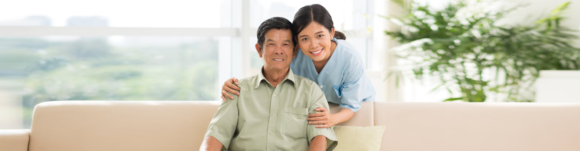 caregiver and an elderly man smiling at the camera